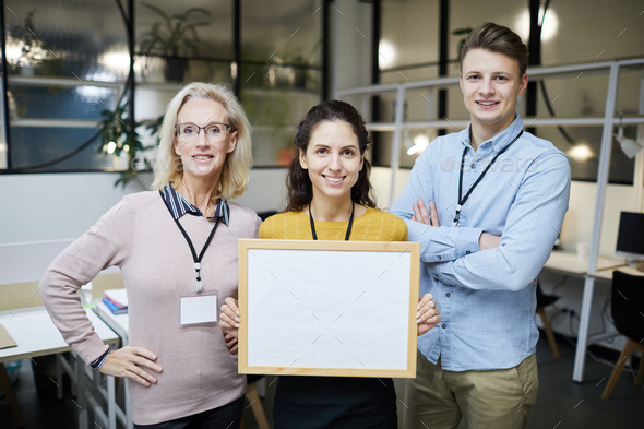 Positive colleagues presenting project using banner - Stock Photo - Images
