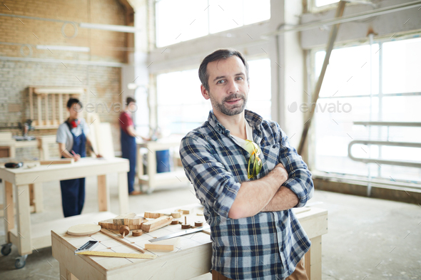Confident workman in carpentry shop - Stock Photo - Images