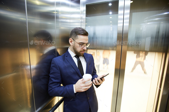 Businessman in elevator - Stock Photo - Images