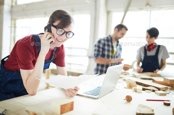 Young carpenter calling customer from workshop - Stock Photo - Images