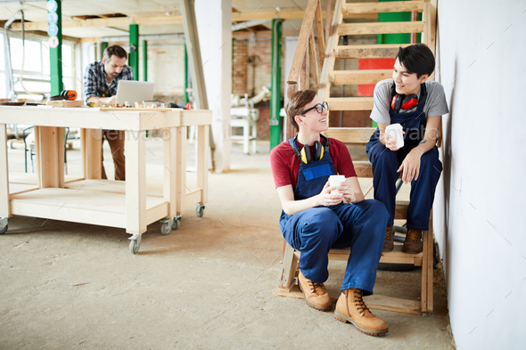 Positive workers drinking coffee in workshop - Stock Photo - Images