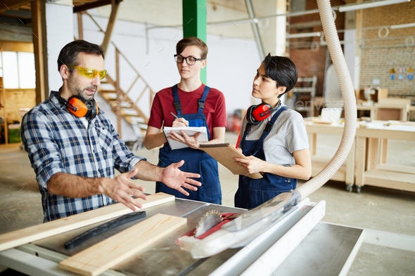 Skilled carpenter working with interns - Stock Photo - Images