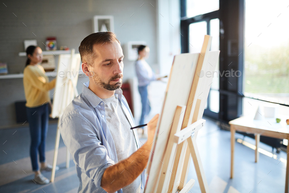 Man painting in studio - Stock Photo - Images