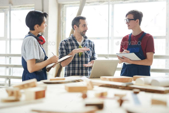 Chief carpenter giving class for interns in workshop - Stock Photo - Images