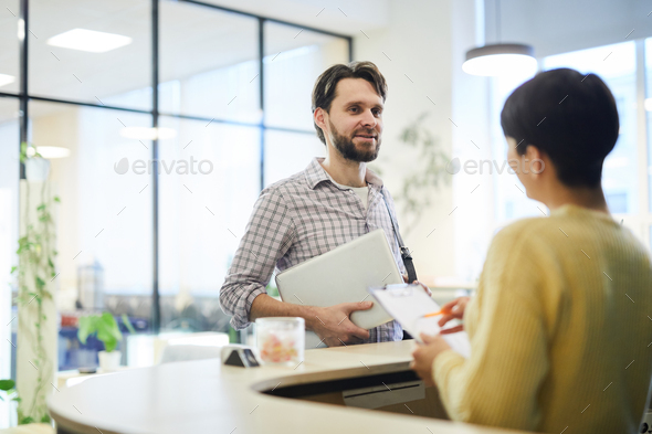 Young programmer talking to hotel receptionist - Stock Photo - Images