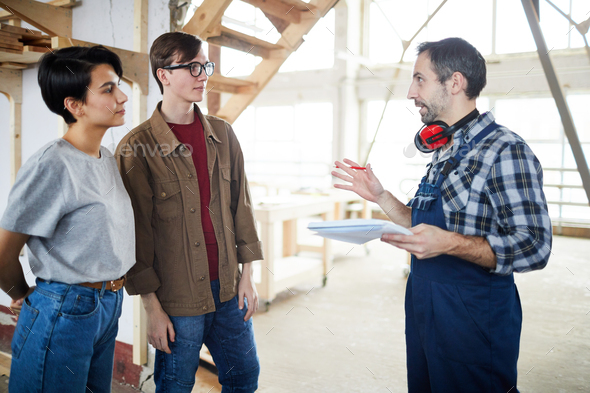 Builder talking to customers - Stock Photo - Images