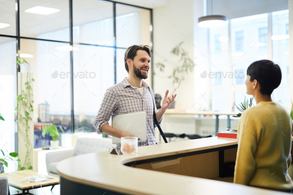 Cheerful man asking receptionist to check in - Stock Photo - Images