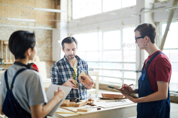 Skilled carpenter holding class for interns - Stock Photo - Images