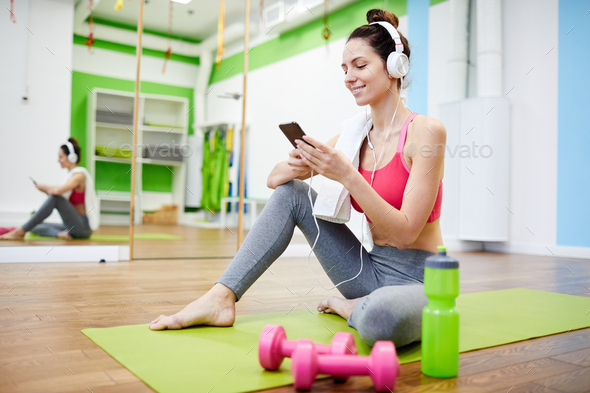 Woman Using Smartphone in Gym - Stock Photo - Images