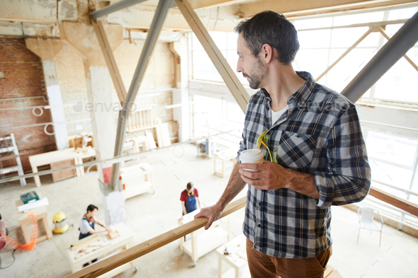 Chief carpenter observing work of joiners - Stock Photo - Images