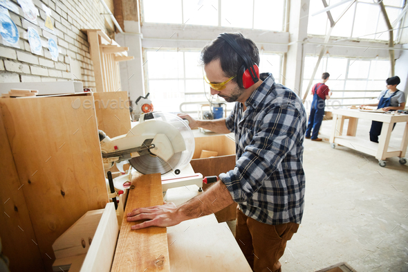 Concentrated man cutting wooden piece - Stock Photo - Images
