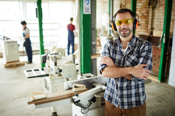 Carpenter in ear protectors standing against cutting machine - Stock Photo - Images