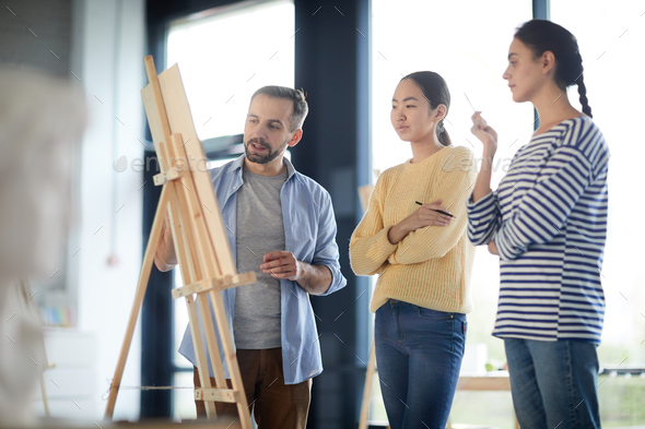 Students and teacher by easel - Stock Photo - Images
