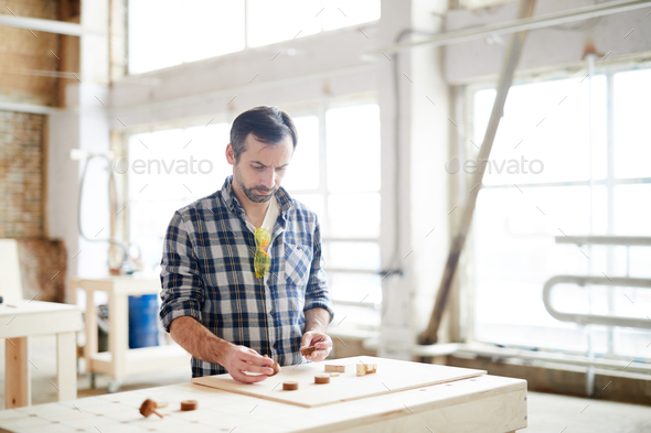 Busy workman comparing small wooden details - Stock Photo - Images