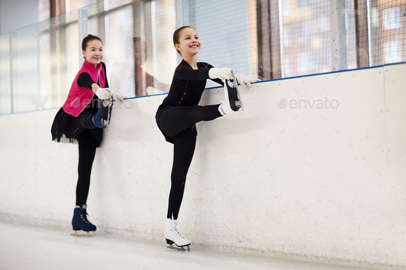 Two Figure Skaters Stretching Legs - Stock Photo - Images