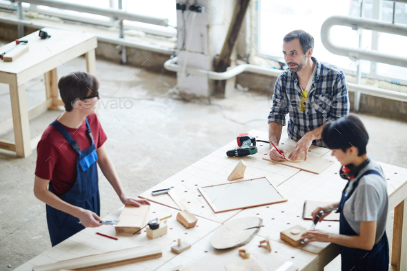 Carpenters chatting while working with wood - Stock Photo - Images