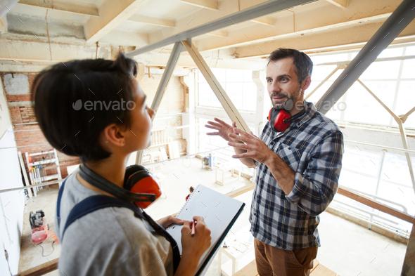 Carpenter explaining tasks to new employee - Stock Photo - Images
