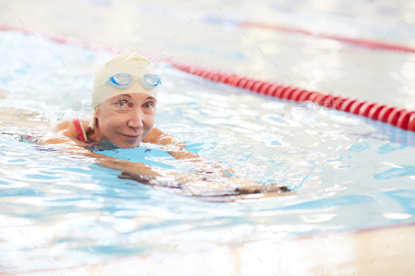 Smiling Senior Woman Swimming in Pool - Stock Photo - Images