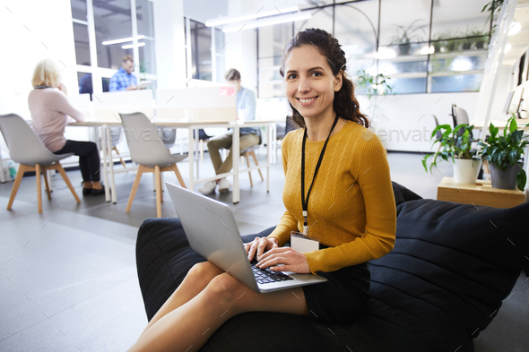 Beautiful woman with badge working in cozy office - Stock Photo - Images