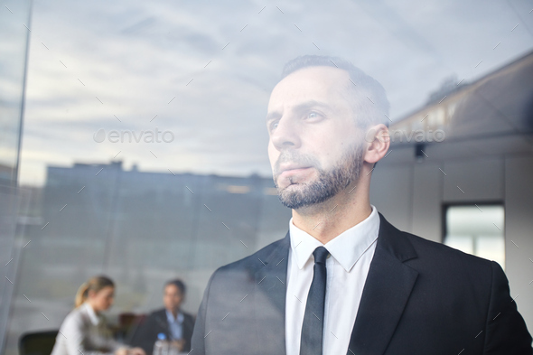 Serious man by window - Stock Photo - Images