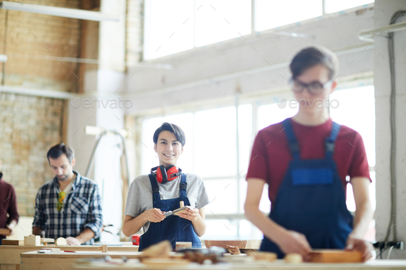 Cheerful lady working in carpentry shop - Stock Photo - Images