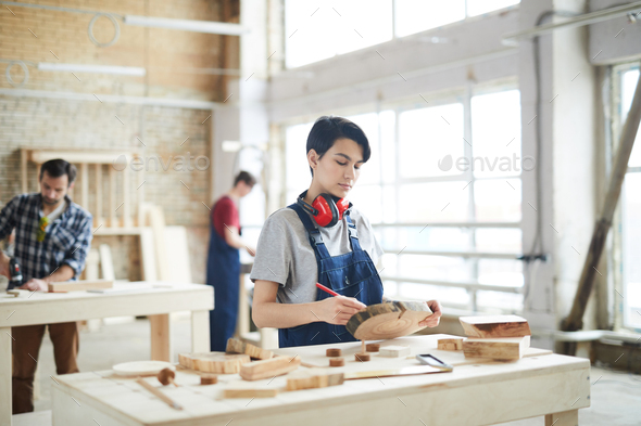 Masculine girl drawing on slice of wood - Stock Photo - Images