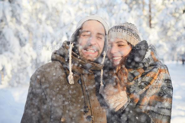 Loving Couple Enjoying Snowfall - Stock Photo - Images
