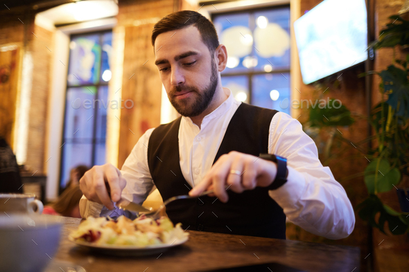 Handsome Businessman Eating in Restaurant - Stock Photo - Images