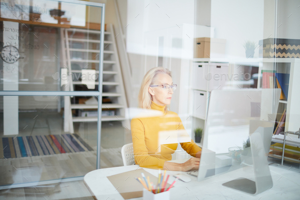 Mature Businesswoman Working behind Glass - Stock Photo - Images