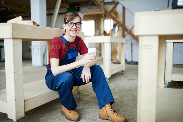 Positive young carpenter drinking coffee - Stock Photo - Images