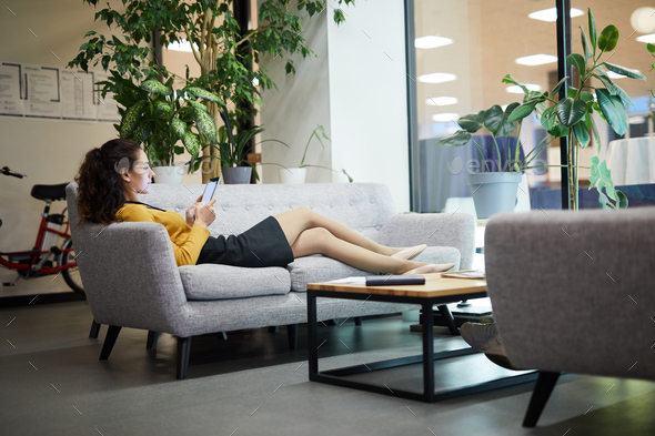 Relaxed lady reading online article in lobby - Stock Photo - Images