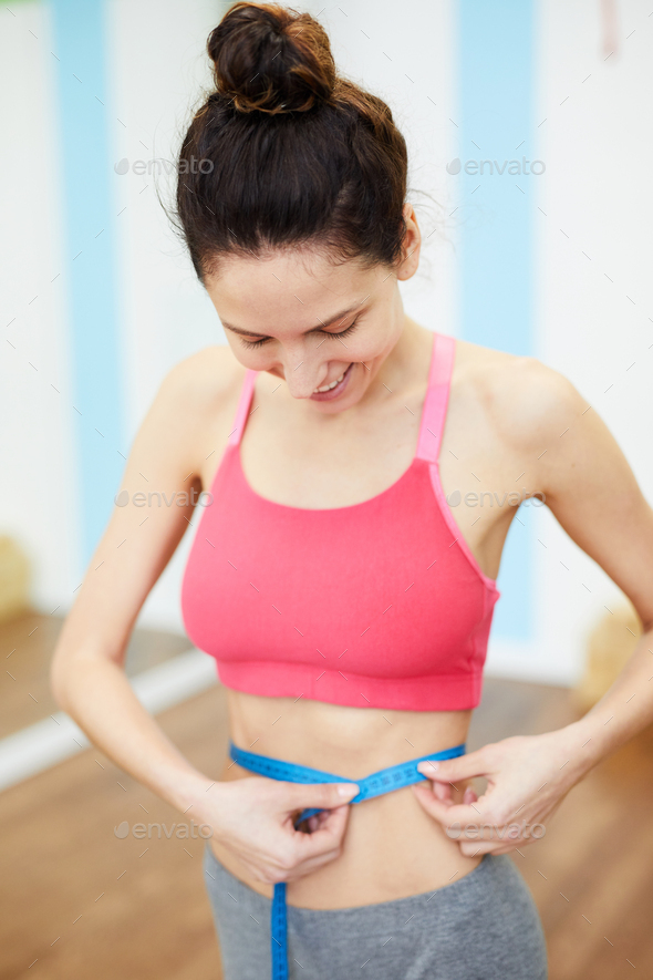 Young Woman Measuring Waist - Stock Photo - Images