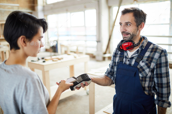 Customer paying builder using nfc technology - Stock Photo - Images