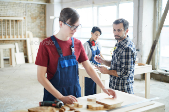 Serious carpentry teacher checking work of students - Stock Photo - Images