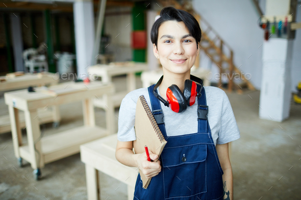 Pretty girl learning about carpentry - Stock Photo - Images
