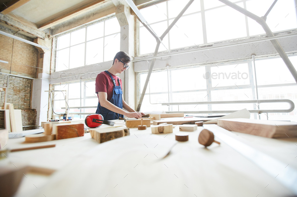 Busy guy in carpentry workshop full of light - Stock Photo - Images