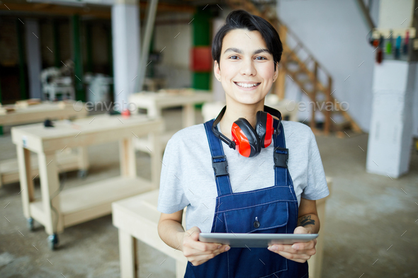 Smiling female carpenter with tablet - Stock Photo - Images