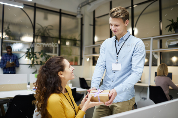 Happy lady accepting gift from colleague - Stock Photo - Images