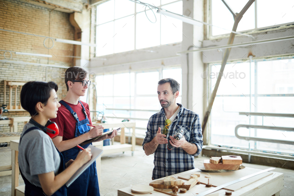 Teaching carpentry students in workshop - Stock Photo - Images