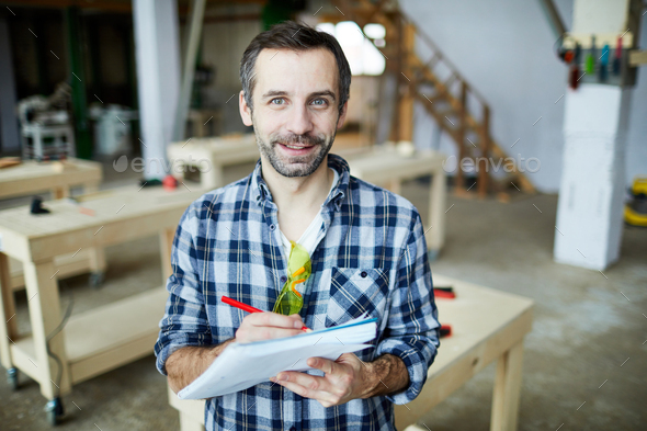 Handsome carpenter developing design of new detail - Stock Photo - Images