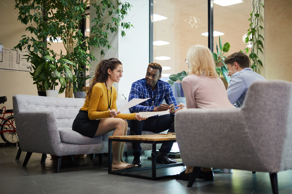 Creative team discussing sales statistics in office - Stock Photo - Images