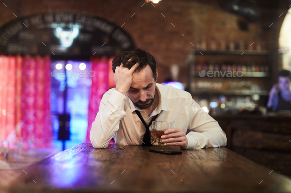 Depressed Man Drinking in Bar - Stock Photo - Images