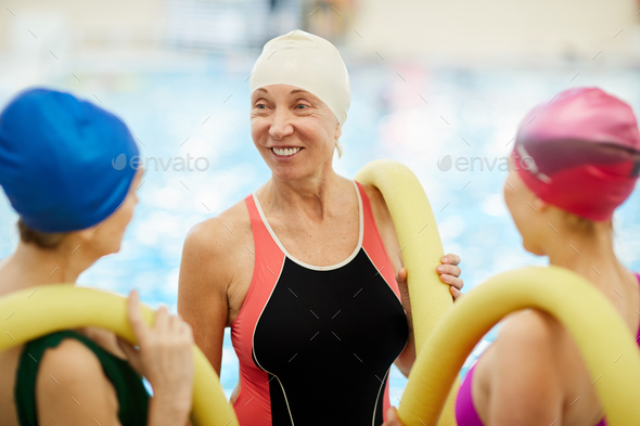 Senior Women Chatting by Pool - Stock Photo - Images