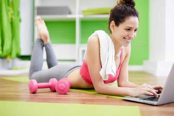 Womn Using Laptop for Workout - Stock Photo - Images