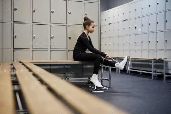 Girl Tying Figure Skates in Dressing Room - Stock Photo - Images