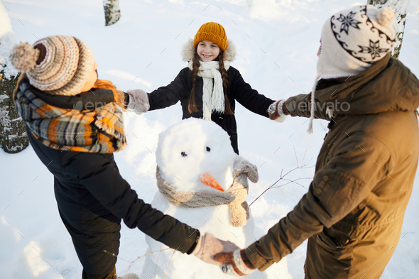 Loving Family around Snowman - Stock Photo - Images