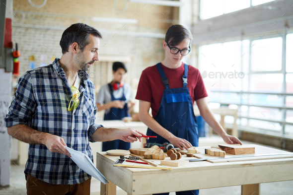 Carpenter giving advice to student in workshop - Stock Photo - Images