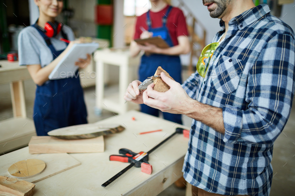 Measuring distance between opposite sides of wooden piece with caliper - Stock Photo - Images