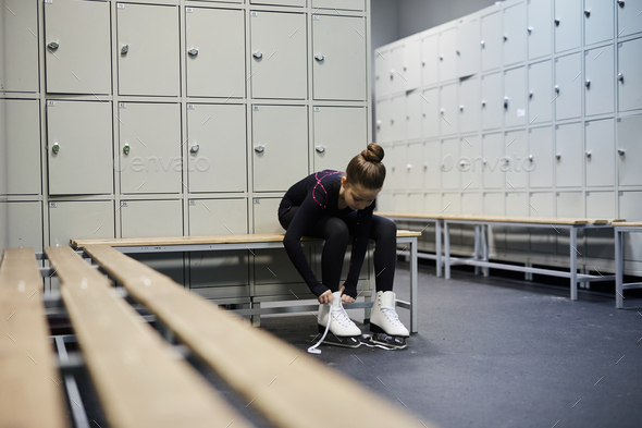 Girl Tying Skates in Dressing Room - Stock Photo - Images