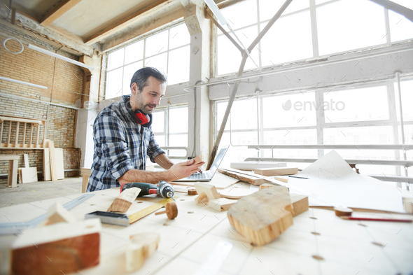 Carpenter searching for information on Internet while checking wooden details - Stock Photo - Images